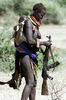 A woman from the nomadic Dinka tribe walk with her baby, while holding on to a AK 47 machine gun, Tuesday June 11, 2002 in Southern Sudan near the border with Kenya.(