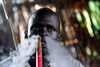 A Sudanese man with tradiotional scars on his face relax with a waterpipe in a market , Friday, Dec. 16, 2005  in Leer in Southern Sudan. Some 2 million people died in the 21 years before the United States helped negotiate peace last January, many in places forgotten by the passage of time, not named on any map, without roads, running water, electricity, schools or health care.(AP Photo/Karel Prinsloo)