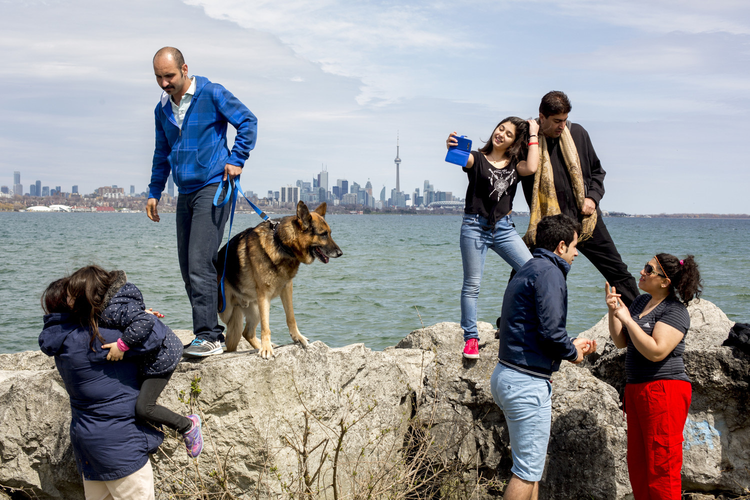 Iranian diaspora in 'Tehranto'.  Iranian refugee families enjoy a Sunday picnic at Toronto Humber Bay Park. From the left: Sarvenaz Fahimi with her daughter and Behzad Abdolahi with his dog. Hana Khanjani taking a selfie with his father Nosrat Khanjani. Arash Tavakoli and Arezoo Victor talking together.