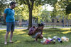 David Fernandez (L) and Audrey Khoo pay their respects next to the makeshift tribute that has been created at Trinity Bellwoods Park, next to the tree where a man died after being hit by a falling branch, in Toronto, Sunday, June 19, 2016.