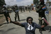 A Kenyan woman hold a Bible as she pray for peace in front of riot police, Sunday,Dec. 30, 2007 during riots in the Mathare slum in Nairobi.