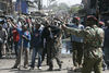 A protestor hide a machete as police arrive , Wednesday, Jan. 2, 2008 during riots in the Mathare slum in Nairobi.