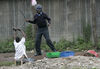 A woman who were washing her laundry when police fired tear gas beg a policeman not to beat her, Thursday, Jan. 17, 2008 during riots in the Mathare slum in Nairobi