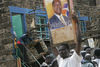 A Kikuyu woman remove her funiture under police guard as opposition suporters threaten them and one hold up a poster of their leader Raila Odinga, Sunday, Jan. 20, 2008 during ethnic fighting in the Mathare slum in Nairobi