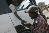 A Kikuyu man look at an identification document of a truck driver to make sure he is from their tribe before they let him pass a roadblock, Monday, Jan. 28, 2008 in Naivasha, Kenya.