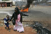 A woman run to saftey with her child past burning barricades, Tuesday, April 8, 2008 during clashes between police and opposition party supporters in the Kibera slum in Nairobi