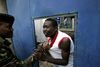A member of the police beat a man, Monday, April 14, 2008 during protest in the Dandora slum in Nairobi, Kenya.