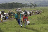 People carry their belongings as they evacuat a refugee camp as people flee fighting, Monday, Oct. 28, 2008 near Kibumba some 40 kilometers north of Goma in eastern Congo