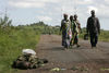 Displaced people walk past the body of a Congolese soldier as they return home, Friday , Oct. 31, 2008 near Kibumba some 40 kilometers north of Goma in eastern Congo.