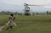 A child run past a U.N helicopter that landed near a makeshift displaced persons camp outside the MONUC base in the village of Kiwanja, 90 kms north of Goma, eastern Congo, Friday, Nov. 7, 2008
