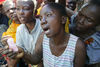 Congolese woman plead with officials to hand them food, Monday, June 2. 2003, at a food distrubution point for displaced people in Bunia, Congo.