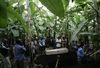 Displaced people gather around the body of Rebecca Yalala,who have had died the day before of complications from diabetes and malaria , as they prepare to bury her in a grove of banana trees near a camp for displaced people, Tuesday, Nov. 18, 2008 in Bulengo near Goma in eastern Congo.