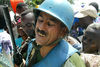An Uruguyan United Nations soldier struggle to pull a woman and her baby to the front of a line, Monday, June 2. 2003, at a food distrubution point for displaced people in Bunia, Congo.
