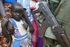 A Congolese child look at a fighter of the rebel Union of Congolese Patriots, UPC, during a rally held by the leader of the UPC Thomas Lubanga , Thursday, June 5. 2003 in Iga Barriere some 25 kilometers outside Bunia, Congo