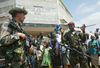 A soldier from the rebel Union of Congolese Patriots speak to a French soldier, Friday, June 6. 2003 outside the UN compound in Bunia, Congo .