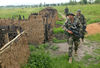 French soldiers walk past huts destroyed in previous tribal fighting, Saturday, June 14, 2003 after they came under fire from unknown gunmen outside Bunia, Congo.