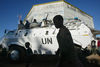 United Nations peacekeepers from Uruguay keep an eye on displaced people walking past their armoured personel carrier outside the UN compound in Bunia , Saturday, May 17. 2003 in the Congo