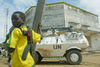 A child fighter of the rebel Union of Congolese Patriots who is currently controling the Congolese town of Bunia stand near an United Nations armoured personel carrier near the UN compound  , Friday, May 30. 2003 in Bunia, Congo.