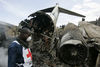 A Congolese Red Cross worker walk amongst the wreckage, Wednesday, April 16, 2008 of a Congolese jetlainer that carshed on takeoff in Goma.