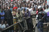 A Congolese riot policeman keep a crowd of onlookers away from the wreckage, Wednesday, April 16, 2008 of a Congolese jetlainer that carshed on takeoff in Goma.