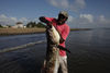 In this Wednesday, Nov. 25, 2009 picture A Kenyan fisherman struggle to lift a fish from the water in Malindi.Fishermen who fish for a living and sportsmen who catch fish for fun say they've seen a rise in fish stocks in northern Kenya and suspect the rise is due to Somali pirates who have forced commercial trawlers off the Somali coast.