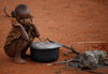 In this Thursday, Oct. 22, 2009 picture a Somali Kenyan boy east a biscuit next to an cooking pot in the settlment of Dela in northen Kenya near the Somali border.