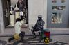 A street performer play the flute to a mime dressed as a futuristic soldier taking a rest , Saturday, April 9, 2011 in downtown Lisbon, Portugal. (AP Photo/Karel Prinsloo)