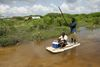 """Somali men use a piece of foam as they float in floodwaters near the village of Marere in southern Somalia, Tuesday, Nov.28, 2006 after the Juba river burst its banks. Fears of a looming war in Somalia are hampering relief efforts for up to one million people hit by severe flooding, a senior U.N. official said Friday. Eric Laroche, the U.N.'s humanitarian chief for Somalia, said a """"corridor of peace"""" is needed so aid can reach 400,000 people who have fled their homes to escape the worst flooding in a decade.(AP Photo/Karel Prinsloo)"""