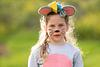girl dressed up as mouse backlit from sun outdoors