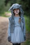 sad girl in grey wolf costume in forest
