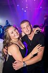 couple posing at bat mitzvah party with purple lights in background