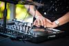 DJ hands on her mixer at outdoor party
