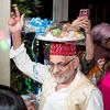 man dancing with plate of deserts on head at Hina