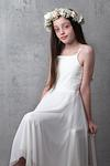 Bat Mitzvah girl in white dress in front of concrete backdrop