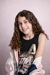 Bat Mitzvah girl in black and pink  in front of pink canvas backdrop Photography studio Modiin