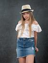 Bat Mitzvah girl in jeans skirt and white top and hat in Modiin Studio