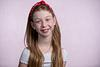 Bat Mitzvah girl with red bow in front of pink canvas backdrop Photography studio Modiin