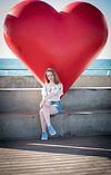 Bat Mitzvah girl at Tel Aviv beach in front of big red heart