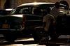 Beautiful light backlits a classic American car and Cubans
