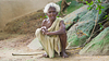 Old aged poor lady sitting on ground in a village