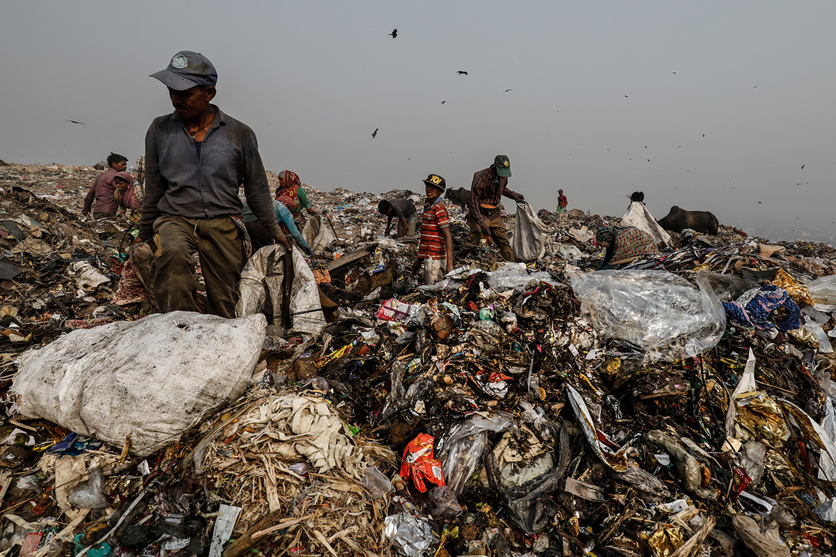 People segregate waste atop a mound of garbage at Bhalswa landfill in New Delhi, India.