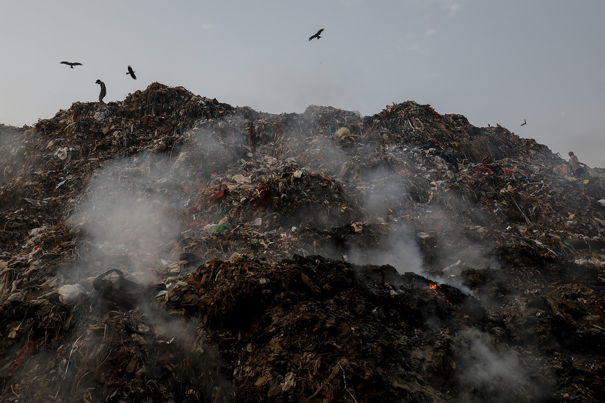Men segregate waste atop a mound of burning garbage at Bhalswa landfill early morning in New Delhi, India.