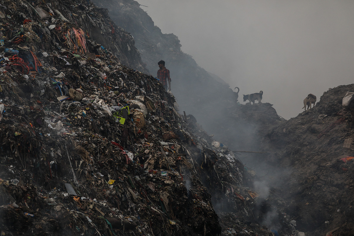 A man segregates waste on a mound of garbage at Bhalswa landfill early morning in New Delhi, India.