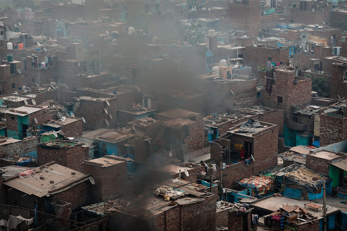 The smoke from burning garbage from Bhalswa landfill rises over a an adjacent settlement in New Delhi, India.