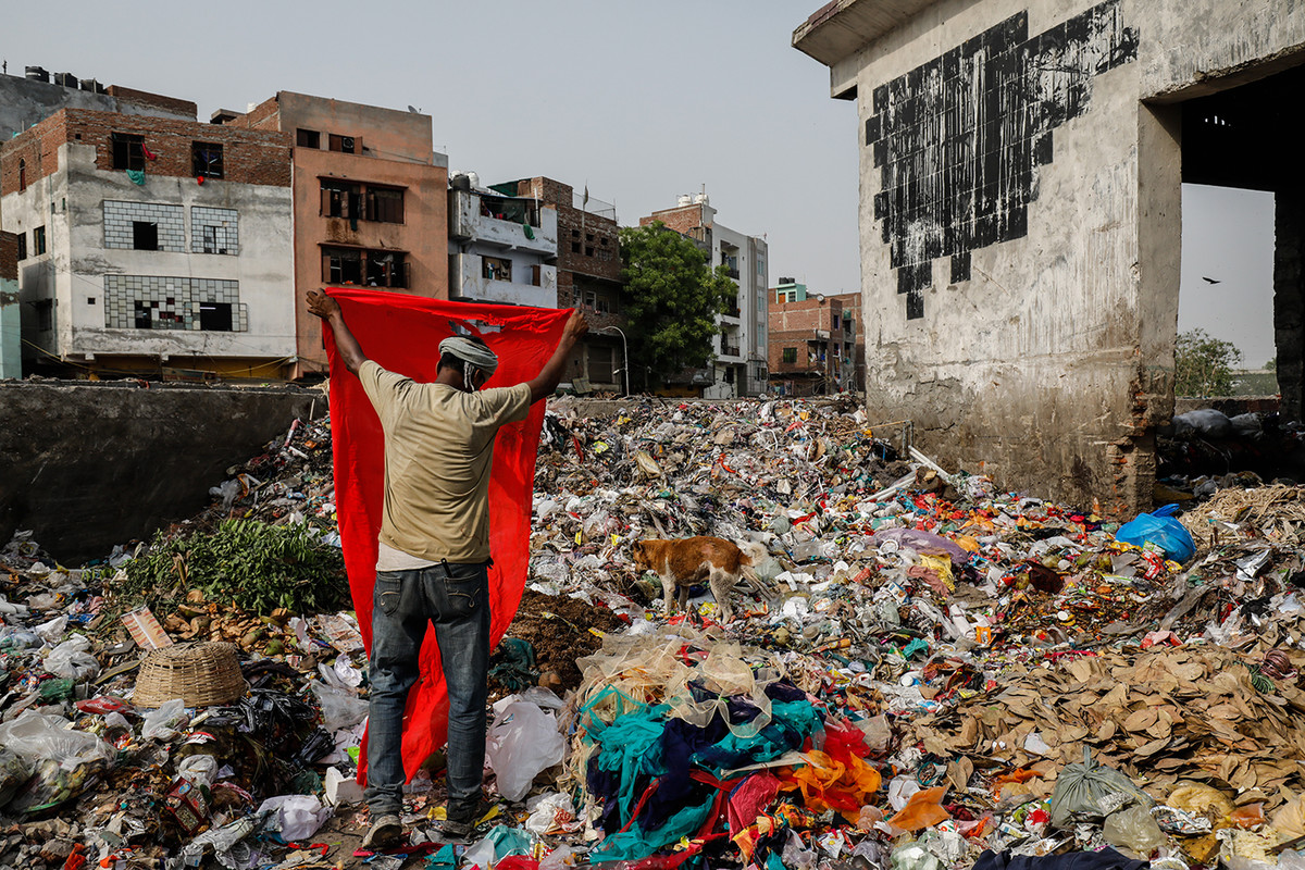 A rag picker segregates cloth from waste at a waste collection point in New Delhi, India.