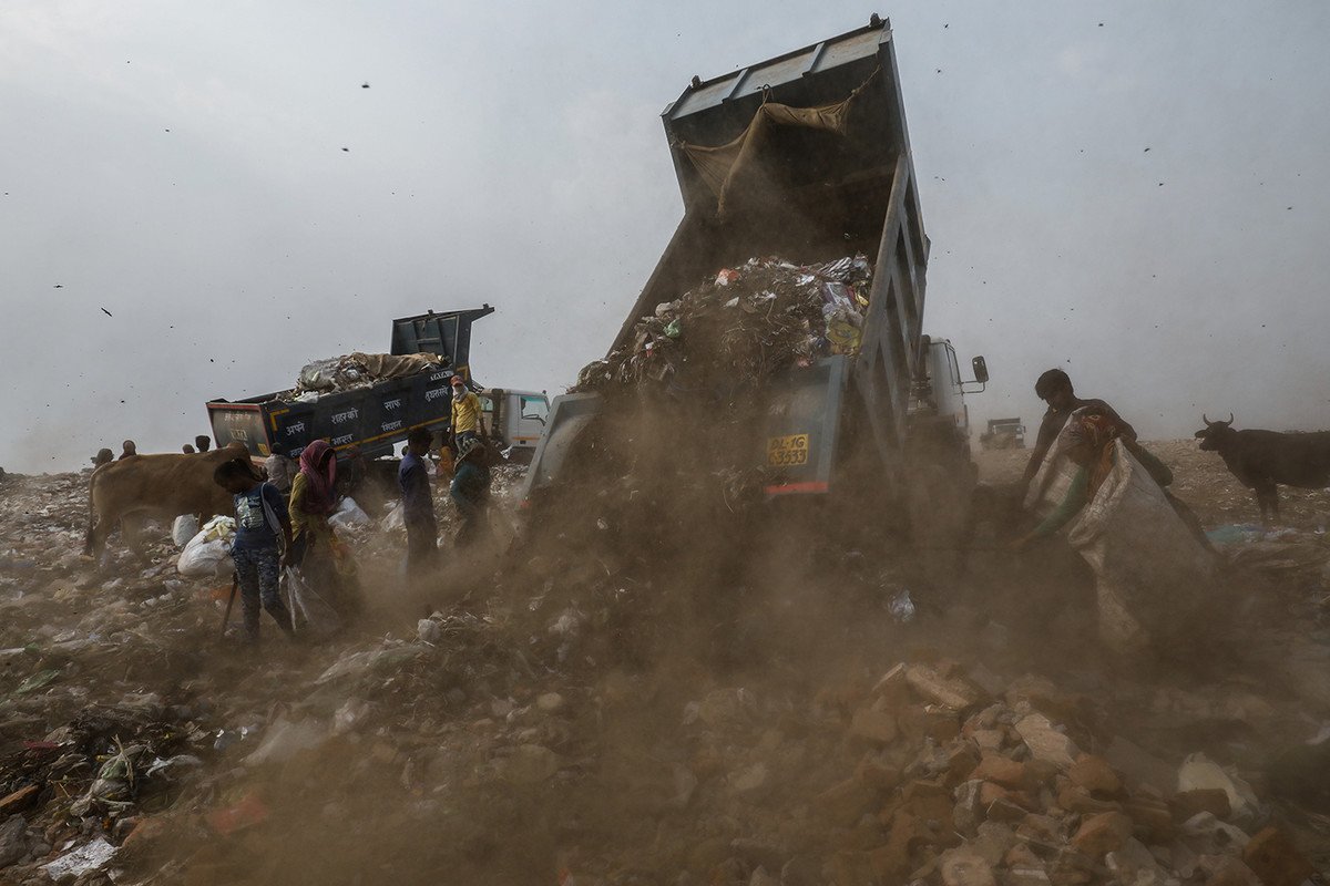 A truck surrounded by rag pickers dumps waste at Bhalswa landfill in New Delhi, India.