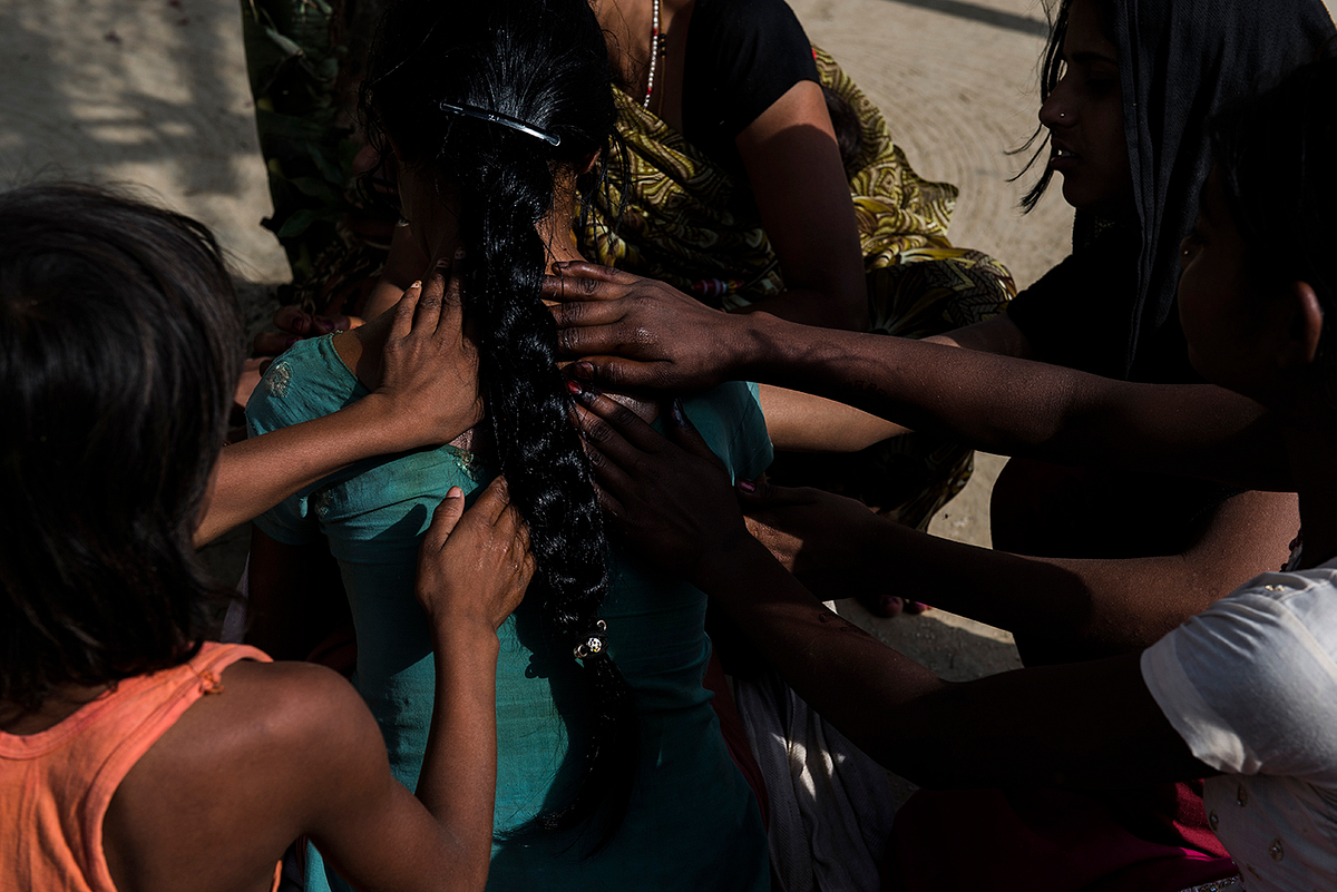 14-year old Muskaan's* family members apply turmeric on her body as the wedding ceremonies commence at her village.