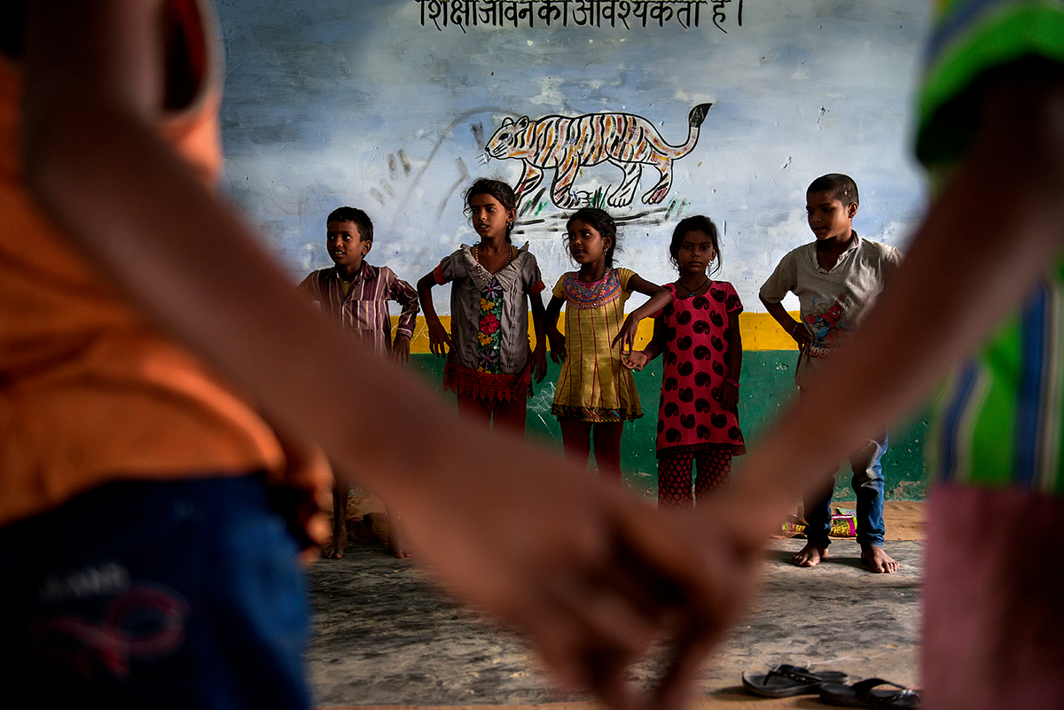 Children participate in a school activity. On the wall is painted, 'Education is the essential of life.'