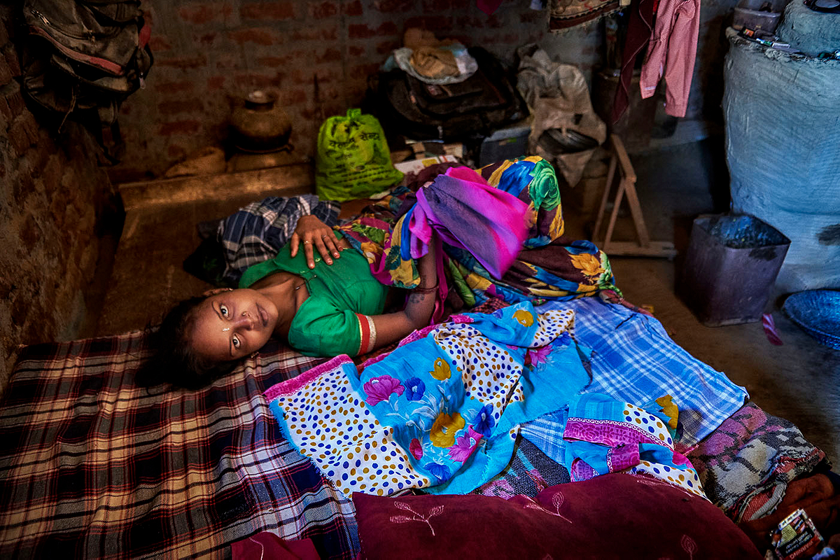 Reena Devi, 18 years old, takes a moment of rest in her bedroom by her 15-day old second child.
