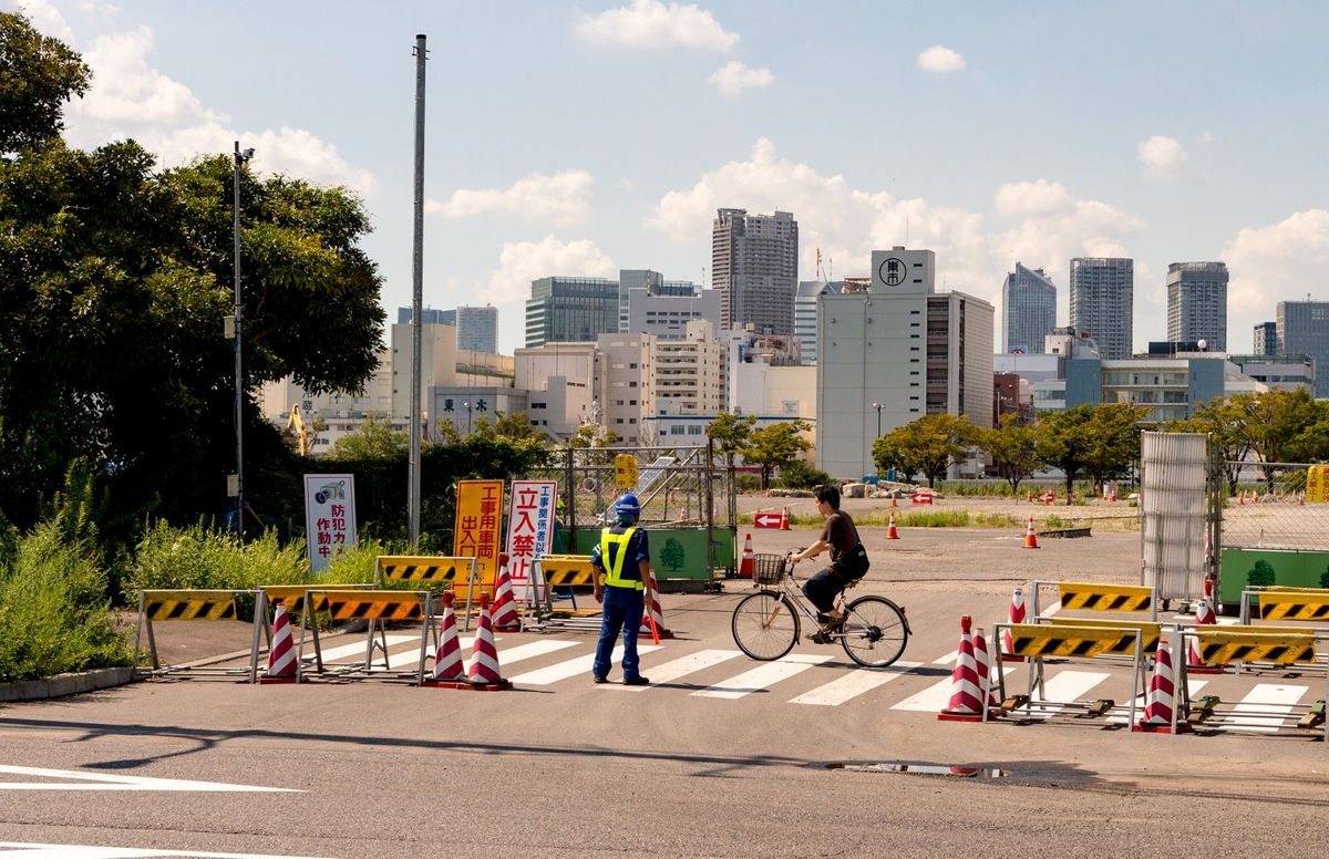 Cyclist passing the entrance for the Olympic Village 2020